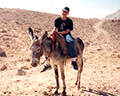 Kids riding donkeys above the Valley of the Kings, Egypt